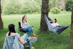 Social distancing. Small group of people enjoying conversation at picnic with social distance in summer park. Friends chilling in hammock and chairs among trees. New normal, safety gatherings