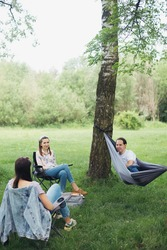 Social distancing. Small group of people enjoying conversation at picnic with social distance in summer park. Leisure activity together in new normal, gatherings following safety protocols