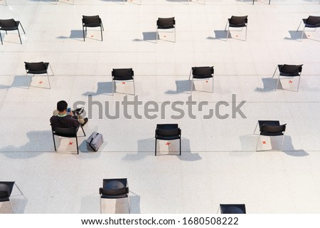 Photo of  Social distancing, transmission of disease, reduce contact and infection during pandemic of Covid-19. A man sit, text on smartphone, wait in rows of empty chairs far apart to slow down virus spreading