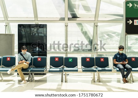Social distancing, two men wearing face mask sitting keeping distance away from each other to prevent covid19 infection during pandemic. Empty chair seat red cross shows avoidance in airport terminal.