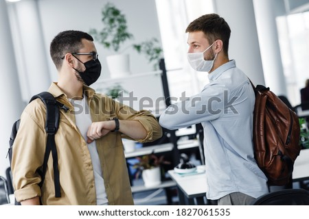 Social distancing without handshake in office during epidemic. Young men in protective masks with backpacks greet each other with elbows in interior of modern office after quarantine, free space