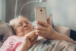 Social isolation, loneliness in older people, health risks. Age-group risk for coronavirus. Lonely elderly woman with smartphone lies in bed at home.