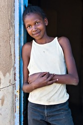Social issues, poverty, African girl, underage farm worker, village near Kalahari desert