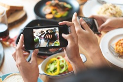 social media and modern people lifestyles. Close up hands of food blogger influencers taking picture of meal dinner post to social media app online in restaurant.
