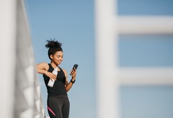 Social media and sport. Smiling athletic african american young woman in fashion sportswear holding bottle of water and looking at smartphone at stadium, free space