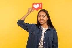 Social media button. Portrait of thoughtful girl in denim shirt holding heart icon on head, follower notification symbol, dreaming of many Likes and internet popularity. indoor studio shot isolated