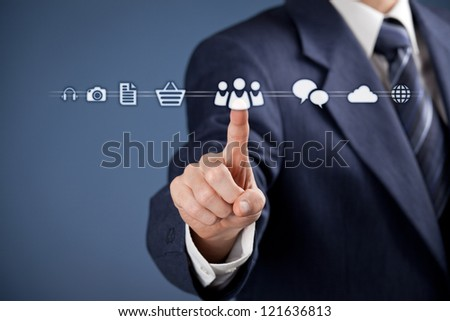 Social media concept - businessman click on virtual icon representing social media. Horizontal composition, blue background, selective focused on hand. - stock photo