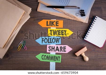 Photo of  social media concept (like, tweet, follow, share, comment). Paper signpost on a wooden desk