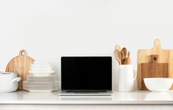 Social media culinary concept, front view of laptop and utensils standing on the modern kitchen countertop