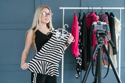 social media influencer at work. blogger explaining style basics. woman holding a stripy top in front of a camera. hobby turned into lucrative business.