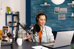 Social media influencer discussing about vlogging in home studio recording podcast. New media star making online fashion content with professional equipment for subscribers audience