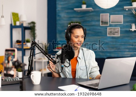 Social media influencer discussing about vlogging in home studio recording podcast. New media star making online fashion content with professional equipment for subscribers audience Photo stock ©