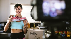 Social media influencer reviewing sports shoe. Smiling young woman vlogging about women's sports shoe and filming herself at home on a video camera.