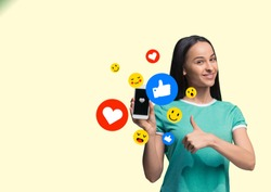Social media interactions on mobile phone. Internet digital marketing, Chating, commenting, liking. Smiles and icons above smartphone screen, that holding by young woman on yellow studio background.