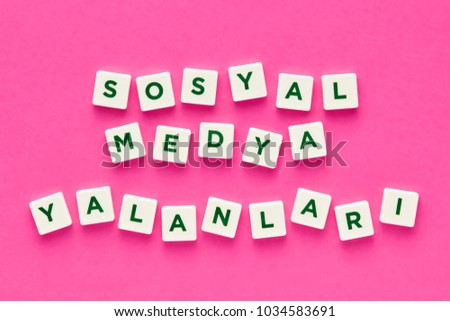 Social media lies words written in Turkish with green letters on white square buttons on pink background. Concept of social media deception and dishonesty. Stok fotoğraf ©