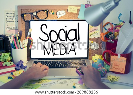 Social Media / Social media concept on laptop, hand typing on laptop keyboard in office interior
