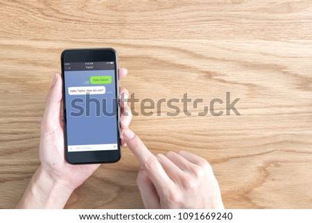 Social network, Chatting and messaging concept, Closeup woman hand holding mobile smartphone on table background, Mock up to screen chat box. #1091669240