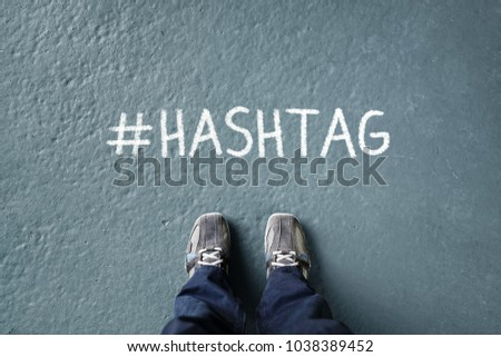 Social network hashtag on floor with man standing looking down concept for trending, marketing and media