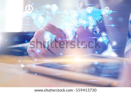 Social networking technology conceptual with businessman using computer tablet and finger touching screen with orange light and show blue world map with people icon symbol connecting the world #559413730