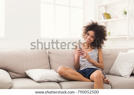 Social networks. Young black woman messaging on smartphone at home, sitting comfortably on beige sofa, copy space