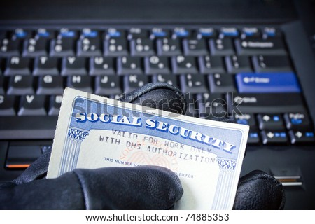 Social Security Card in computer hacker's hand, internet and  identity theft