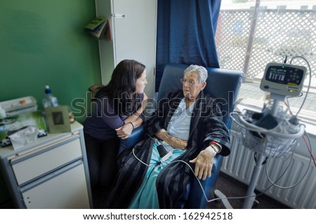 Social worker visit sick old male patient in hospital
