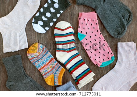 Socks of fine jersey. View from above. Many socks on a wooden background. Socks of different colors and patterns. Clothes for the cold seasons. Knitted clothing. Socks with ornament. - Shutterstock ID 712775011