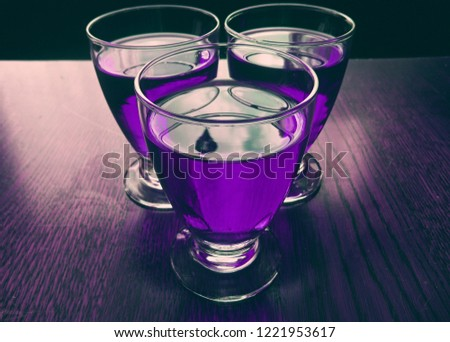 Soda beverages in vintage glasses standing closely next to each other. Drinks have a purple color. Drinks standing on a purple wooden surface. Food and beverage concept. #1221953617
