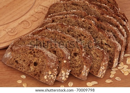 Soda bread loaf in slices next to a carved wooden bread board with loose oat flakes.