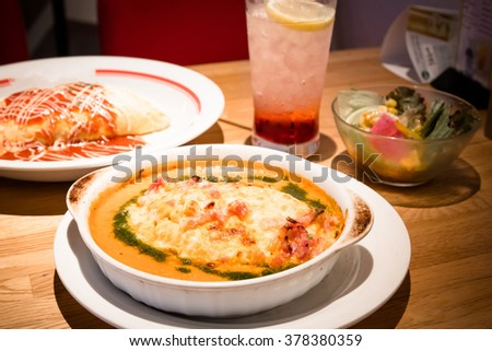 Soda drinking and Golden lasagna with meat, tomatoes, cheese sauce and pasta in alternating layers on a wooden board garnished with basil - warm and dark tone.