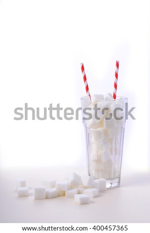 Soda glass of white sugar cubes with red and white straws on white wooden table  Stok fotoğraf ©