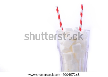 Soda glass of white sugar cubes with red and white straws on white wooden table, close up with copy space.  Stok fotoğraf ©
