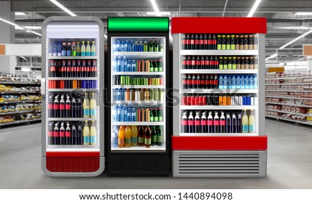 Soda pop drinks and soft drinks in Fridge. Glass door fridge Horizontal photo mockup Soda pop cans and plastic bottles in vertical freezer at supermarket. Suitable for presenting new cans and bottles