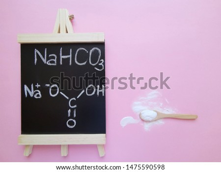 Sodium bicarbonate molecule, known as baking soda. Structural chemical formula written on a black chalkboard with spoonful of bicarbonate powder. NaHCO3  is a salt composed of Na, H, C and O atoms. #1475590598