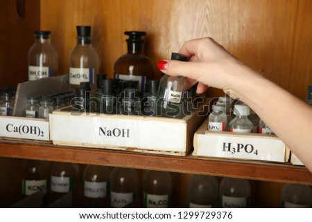 Sodium hydroxide bottle in hand   hand pulls out a bottle with NaOH.  bottles with chemicals H3PO4, Ca(OH)2 Calcium hydroxide, Sodium hydroxide, Orthophosphoric acid on the shelf