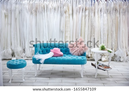 sofa and small chair on the background of wedding dresses