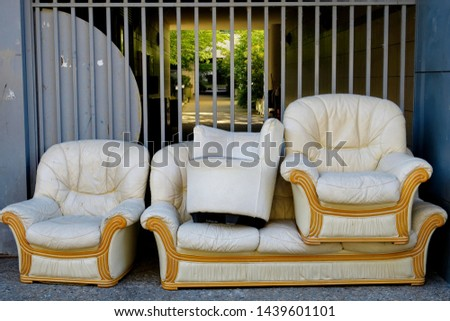 Sofa, armchairs, pouf. Furniture covered with white leather thrown in the street on a sidewalk.    #1439601101