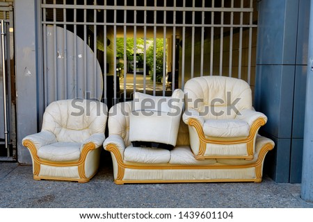 Sofa, armchairs, pouf. Furniture covered with white leather thrown in the street on a sidewalk.    #1439601104