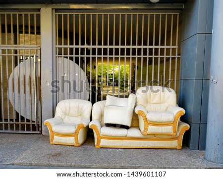 Sofa, armchairs, pouf. Furniture covered with white leather thrown in the street on a sidewalk.    #1439601107