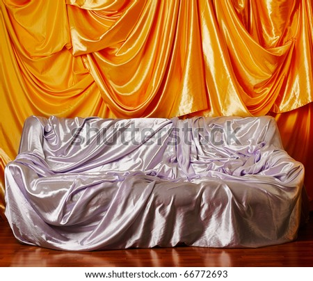 sofa covered with silver silk cloth, wall decorated with golden silk on background