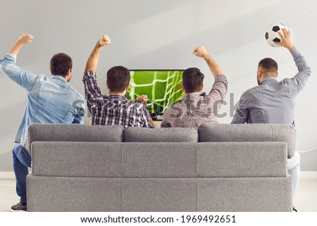 Sofa experts. Back view of male friends gathered at home to watch a football match sitting on the couch in front of the big screen TV. Men actively support their favorite team and comment on the match