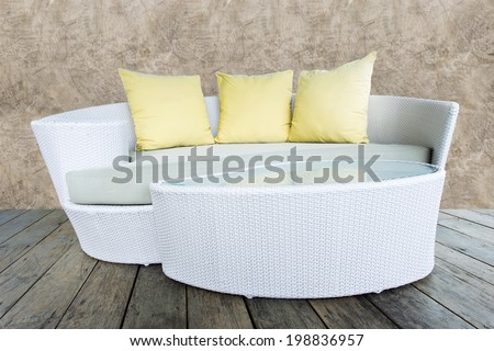 sofa furniture weave bamboo stick chair with yellow pillows on wood and grunge concrete wall