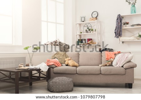 Photo of  Sofa in messy living room with many stack of clothes. Disorder and mess at home, copy space