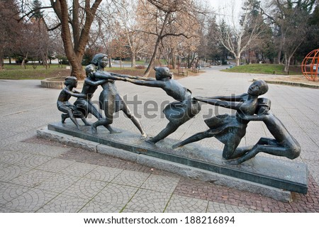 SOFIA, BULGARIA - JANUARY 2: Outdoor sculpture with children entertained in the park, dragging each other. on January 2, 2013. The population of Bulgaria is 7,364,570 people.