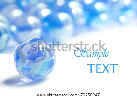 Soft abstract image of blue marbles on white background with copy space. Macro with extremely shallow dof.