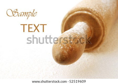 Soft abstract image of wooden rolling pin dusted with flour on white background.  Macro with extremely shallow dof.
