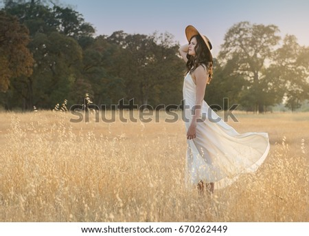 Soft and dreamy image of a young woman with blowing dress in grassy field at sunset