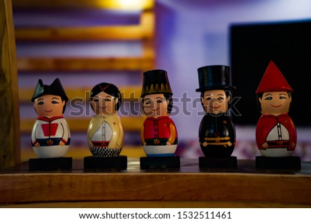 Soft and selected focus image of collectible wooden dolls in traditional of Royal Yogyakarta troop's outfit, set on the rack of a souvenir shop.