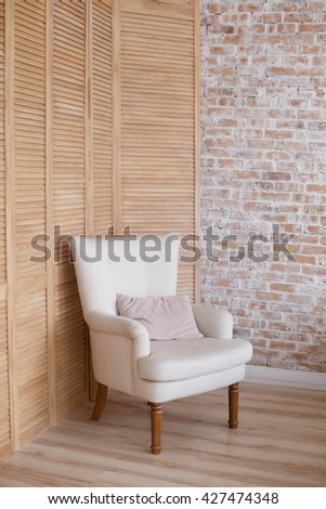soft armchair near brick and wooden wall. Arm-chair with fabric upholstery