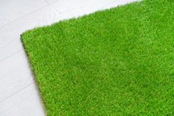Soft artificial grass carpet lying on the white wooden floor
